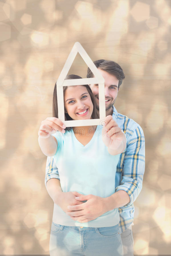 Composite image of happy young couple with house shape. Happy young couple with house shape against light glowing dots design pattern royalty free stock photos