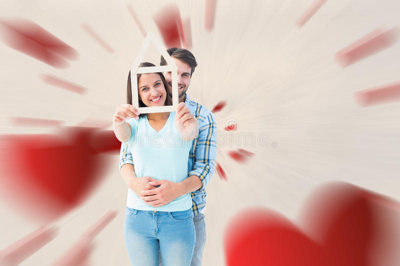 Composite image of happy young couple with house shape. Happy young couple with house shape against love heart pattern stock images
