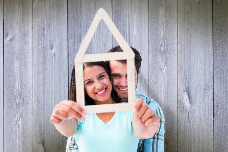 Composite image of happy young couple with house shape. Happy young couple with house shape against wooden planks royalty free stock image