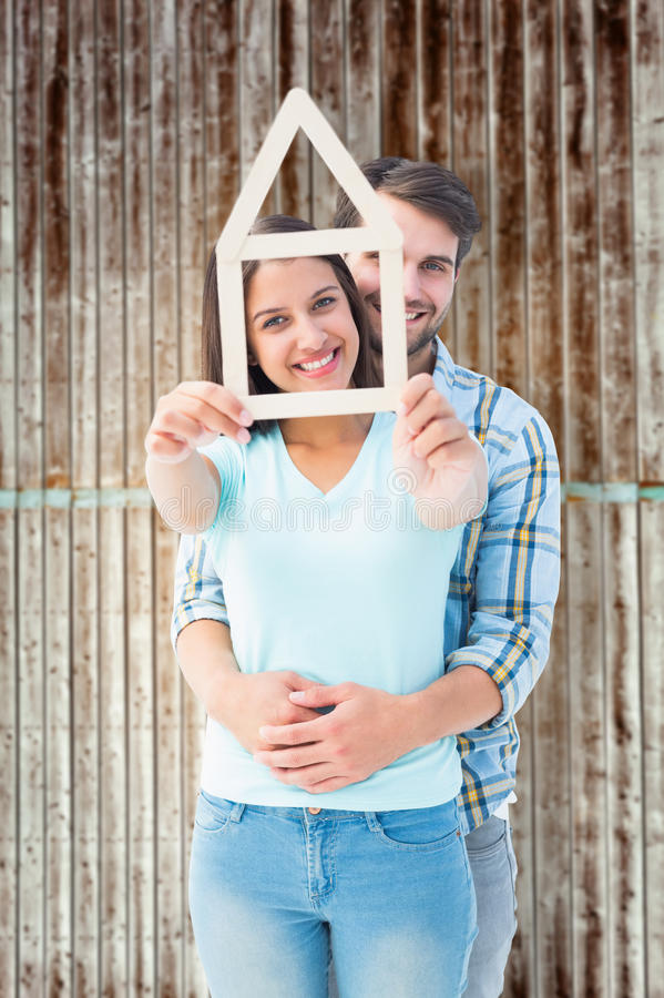 Composite image of happy young couple with house shape. Happy young couple with house shape against wooden planks royalty free stock images