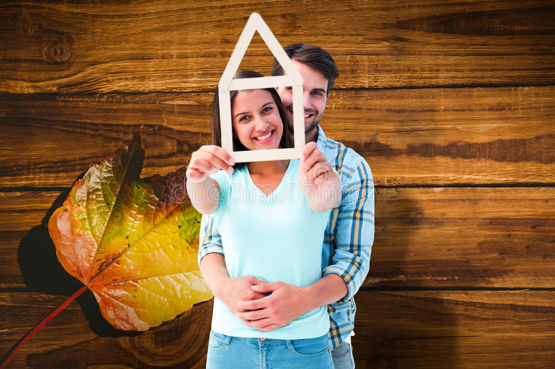 Composite image of happy young couple with house shape. Happy young couple with house shape against wooden table with autumn leaves stock photo