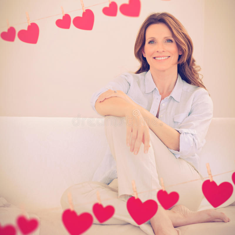 Composite image of hearts on line. Hearts on line against smiling mature woman sitting on sofa royalty free stock image