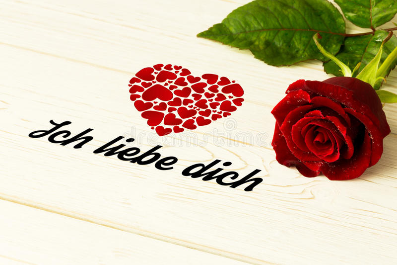 Composite image of ich liebe dich. Ich liebe dich against red rose on wood stock illustration