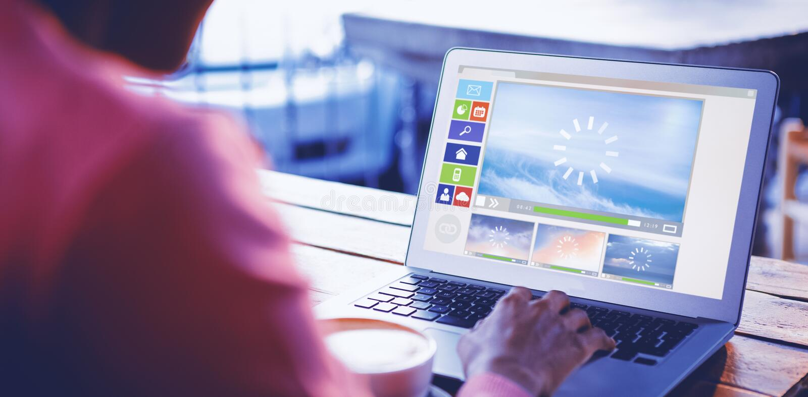 Composite image of illustration of various video and computer icons. Illustration of various video and computer icons against woman using laptop in cafe royalty free stock photos