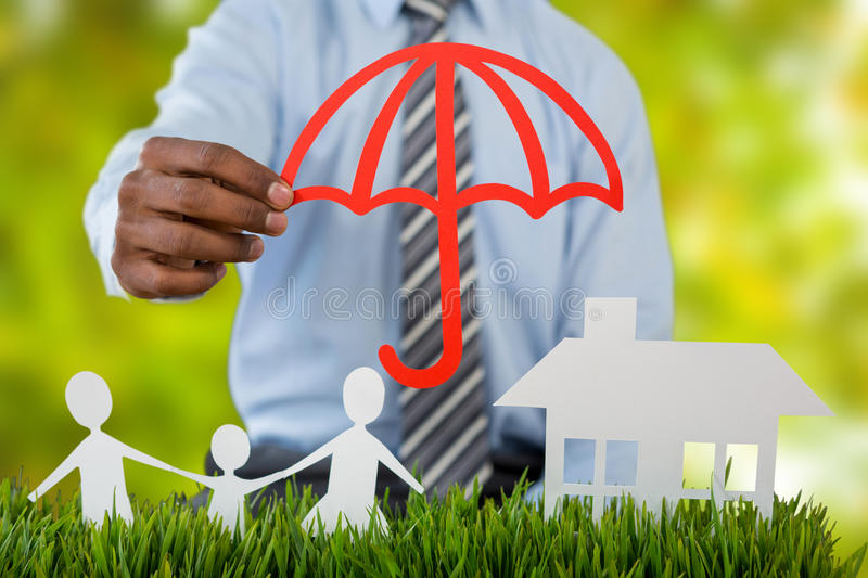 Composite image of insurer protecting family by a red umbrella royalty free stock photos