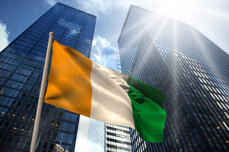 Composite image of ivory coast national flag. Ivory coast national flag against low angle view of skyscrapers stock illustration