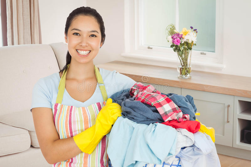 Composite image of laughing woman holding laundry basket stock image