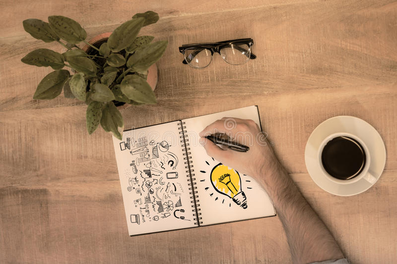 Composite image of light bulb. Light bulb against man writing in notepad stock photo