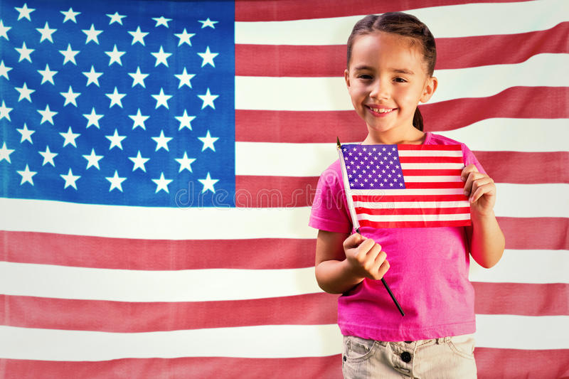 Composite image of little girl with american flag. Little girl with american flag against rippled us flag royalty free stock image