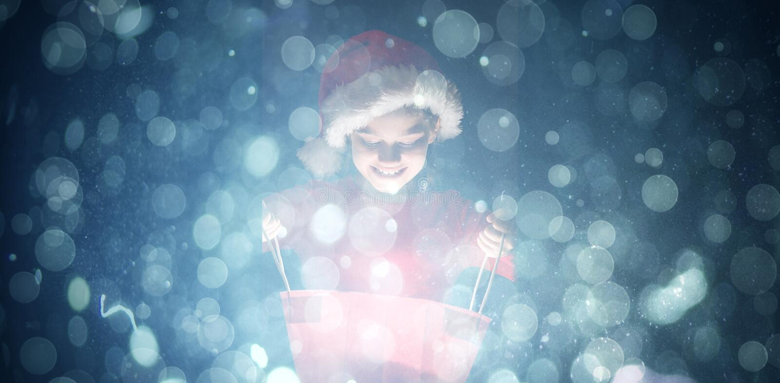 Composite image of little girl opening a magical christmas gift stock photography