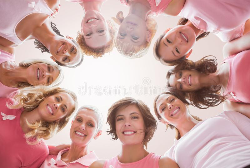 Composite image of low angle portrait of female friends supporting breast cancer. Low angle portrait of female friends supporting breast cancer against neutral royalty free stock photos