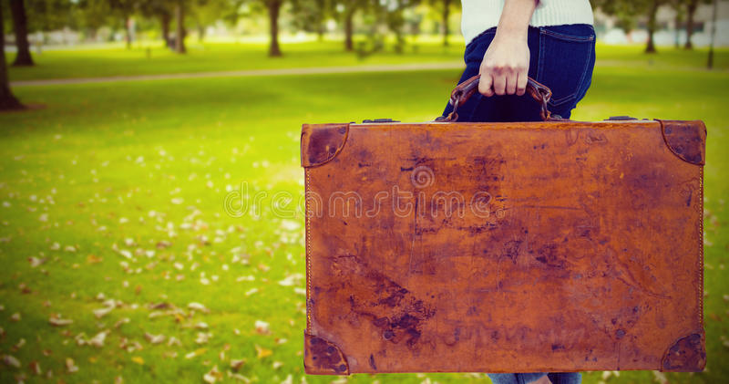 Composite image of low section of woman holding vintage suitcase. Low section of woman holding vintage suitcase against park royalty free stock photo