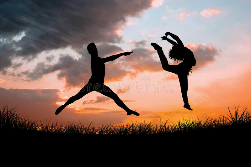Composite image of male ballet dancer jumping. Male ballet dancer jumping against sun set stock photos