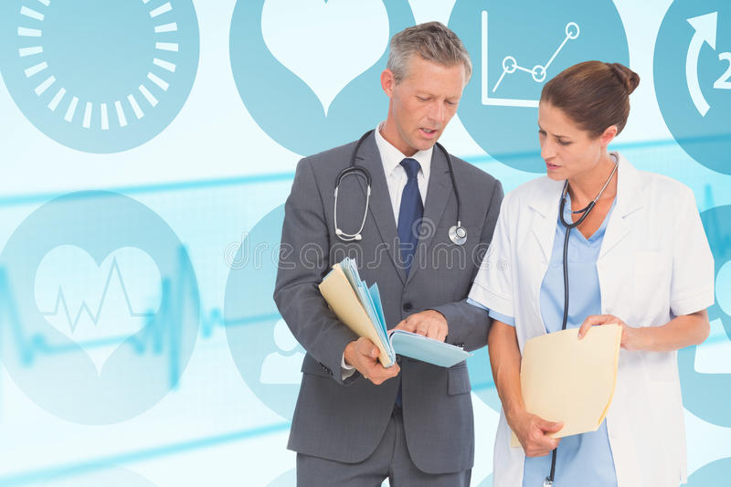 Composite image of male and female doctors discussing over reports royalty free stock photo