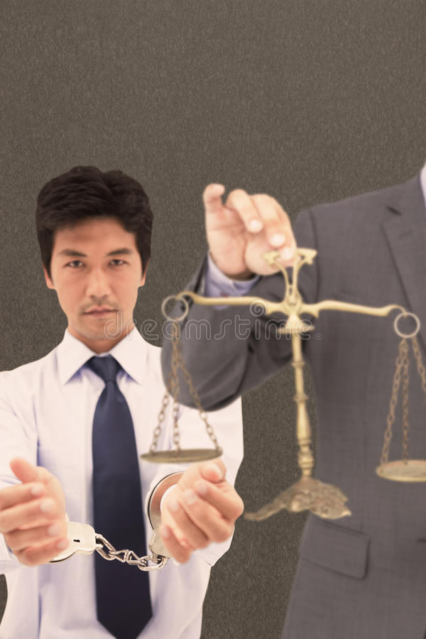 Composite image of male lawyer holding scale and gavel against white background. Male lawyer holding scale and gavel against white background against grey royalty free stock photo