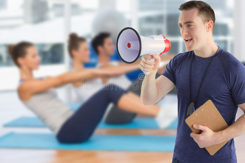 Composite image of male trainer yelling through the megaphone royalty free stock photo