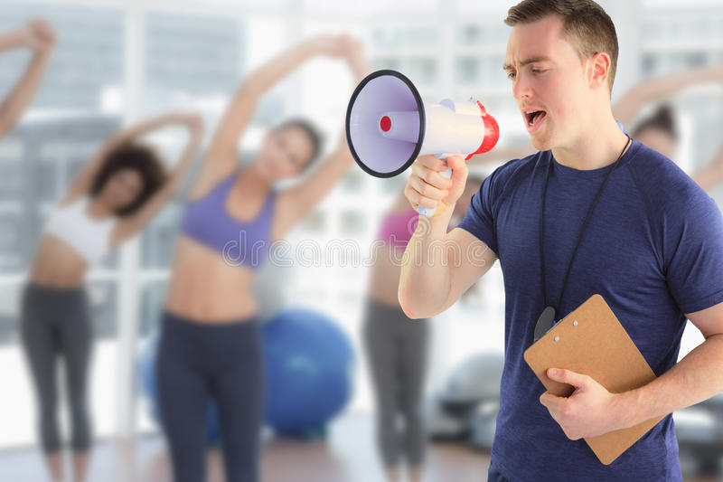 Composite image of male trainer yelling through the megaphone stock photography