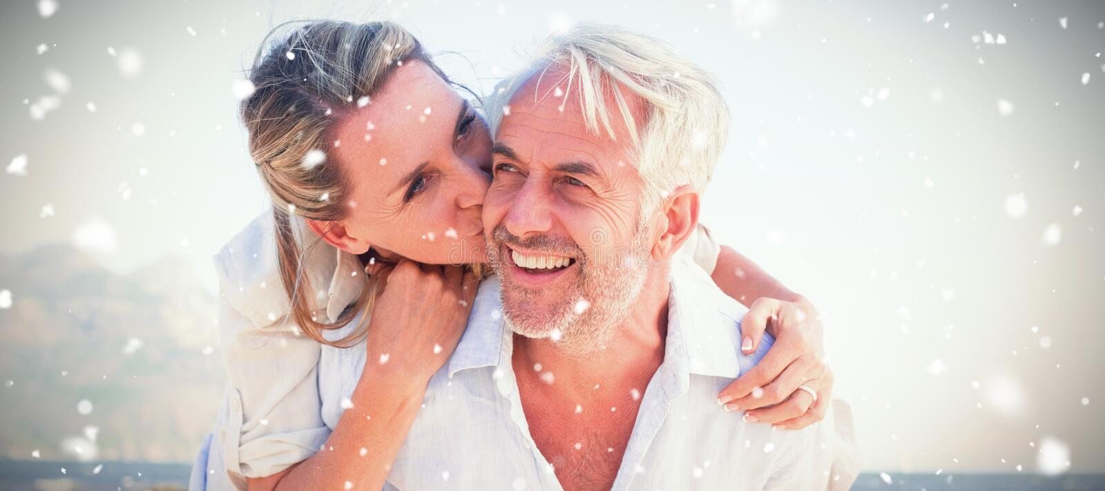 Composite image of man giving his smiling wife a piggy back at the beach royalty free stock photo