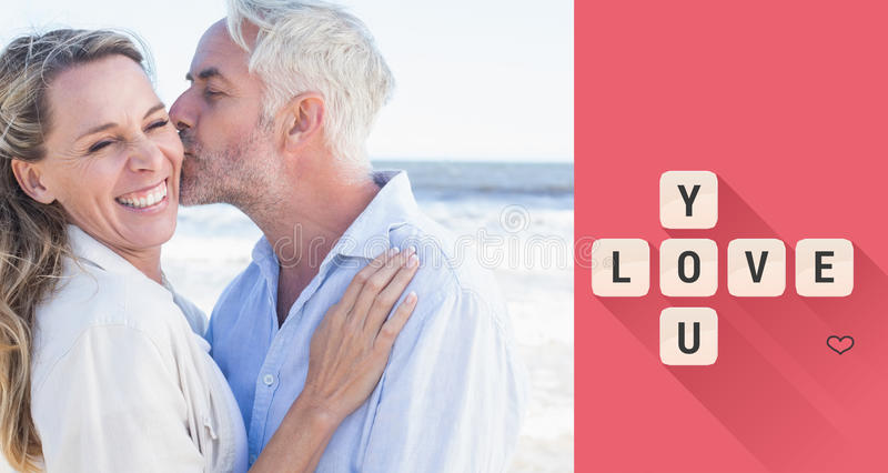 Composite image of man kissing his smiling partner on the cheek at the beach. Man kissing his smiling partner on the cheek at the beach against love you tiles royalty free illustration