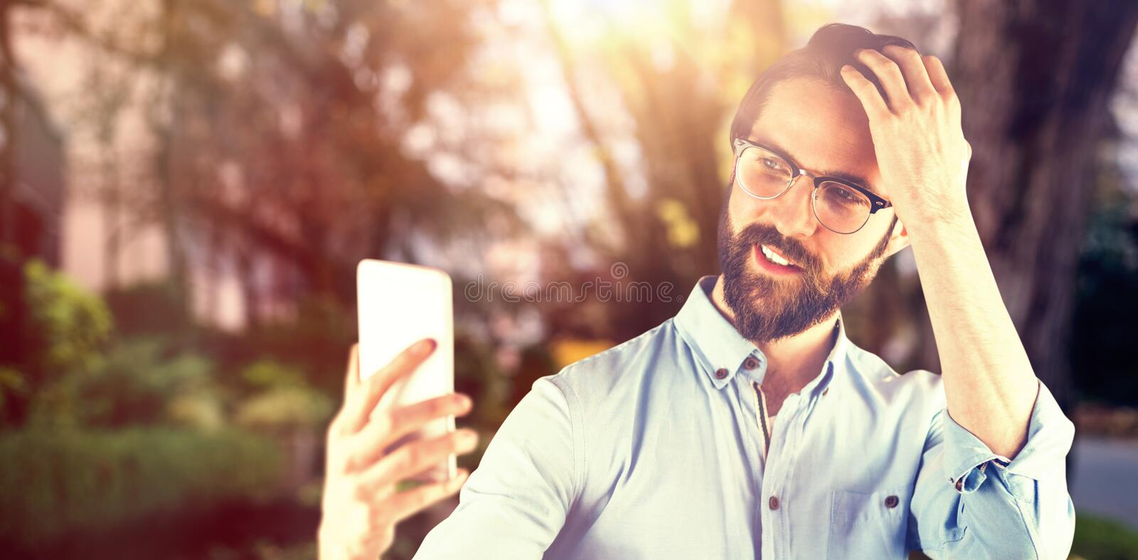 Composite image of man taking selfie with hand in hair royalty free stock images