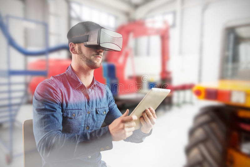 Composite image of man using a virtual reality device. Man using a virtual reality device against red and yellow machineries in factory royalty free stock photography