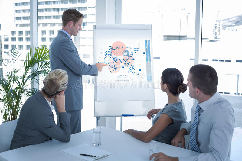 Composite image of manager presenting whiteboard to his colleagues royalty free stock photography