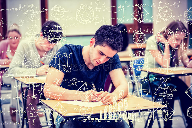 Composite image of maths. Maths against students in an exam stock photos