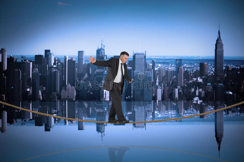 Composite image of mature businessman doing a balancing act on tightrope. Mature businessman doing a balancing act on tightrope against mirror image of city stock image