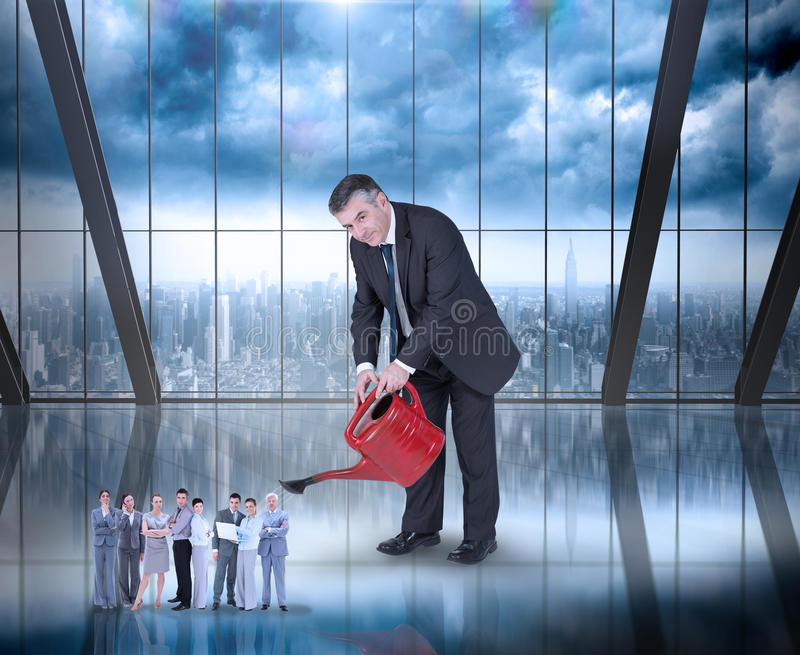 Composite image of mature businessman watering tiny business team. Mature businessman watering tiny business team against room with large window looking on city stock photography