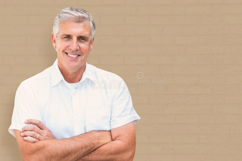 Composite image of mature man smiling. Mature man smiling against white wall stock photos