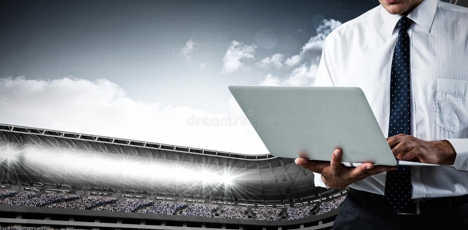 Composite image of mid-section of business man using a laptop stock photos