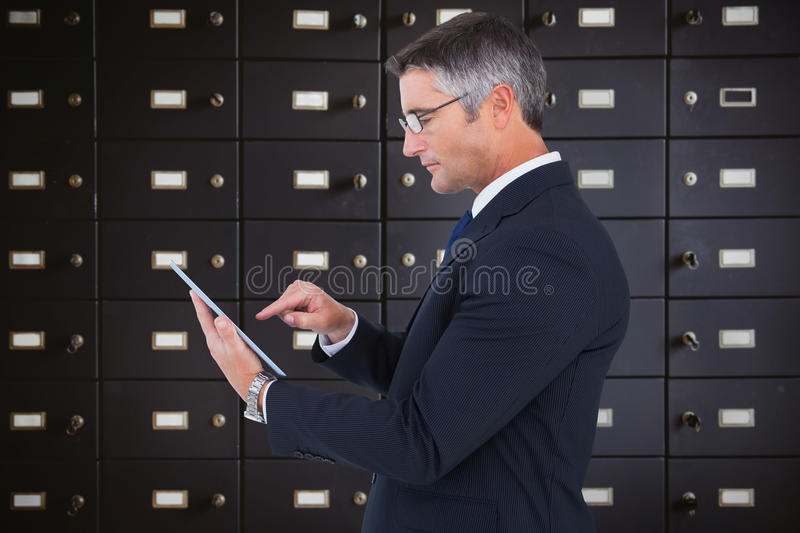 Composite image of mid section of a businessman touching tablet stock image