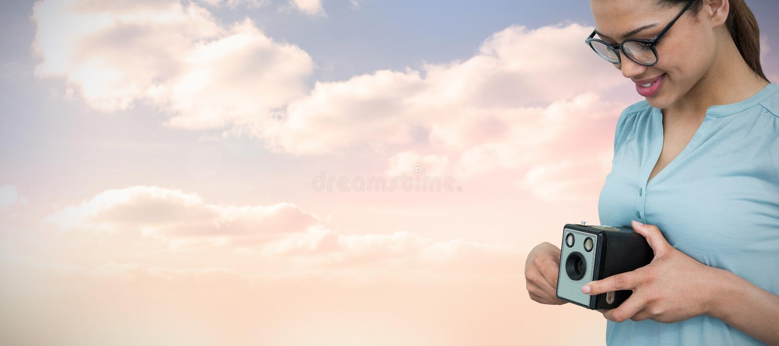 Composite image of mid section of happy female photographer holding vintage camera stock photo