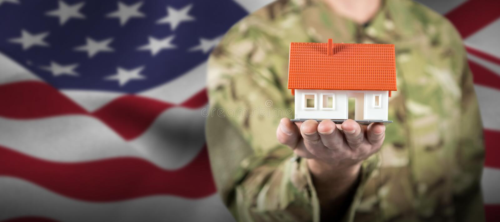 Composite image of mid section of soldier holding model house. Mid section of soldier holding model house against focus on usa flag royalty free stock photo