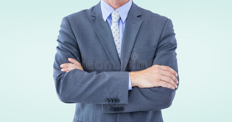 Composite image of midsection of businessman standing arms crossed stock photography