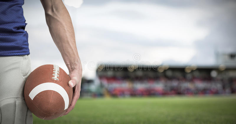 Composite image of midsection of sports player holding ball. 3D Midsection of sports player holding ball against pitch stock images