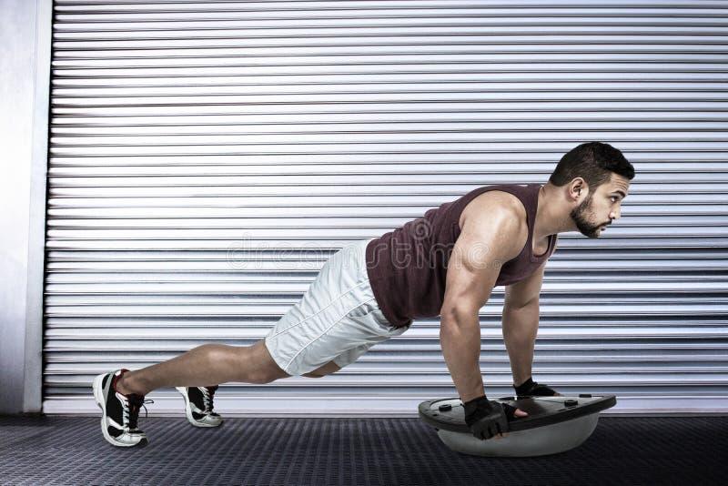 Composite image of muscular man doing bosu push ups stock photo