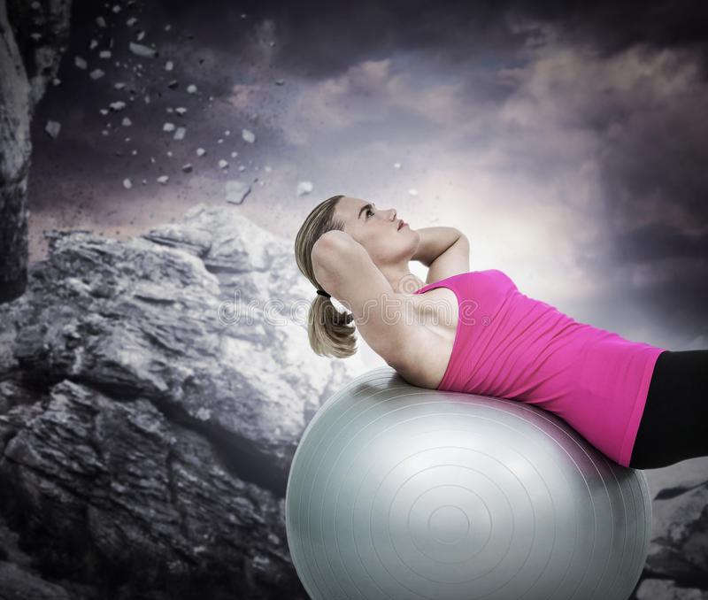 Composite image of muscular woman exercising on ball. Muscular woman exercising on ball against rock crashing down from cliff royalty free stock photography