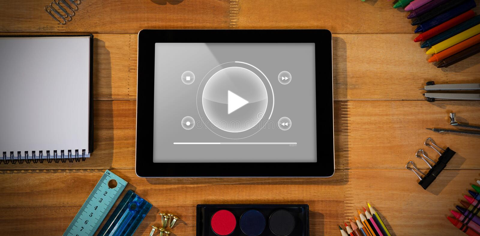 Composite image of music player interface. Music player interface against digital tablet with various stationery stock photography