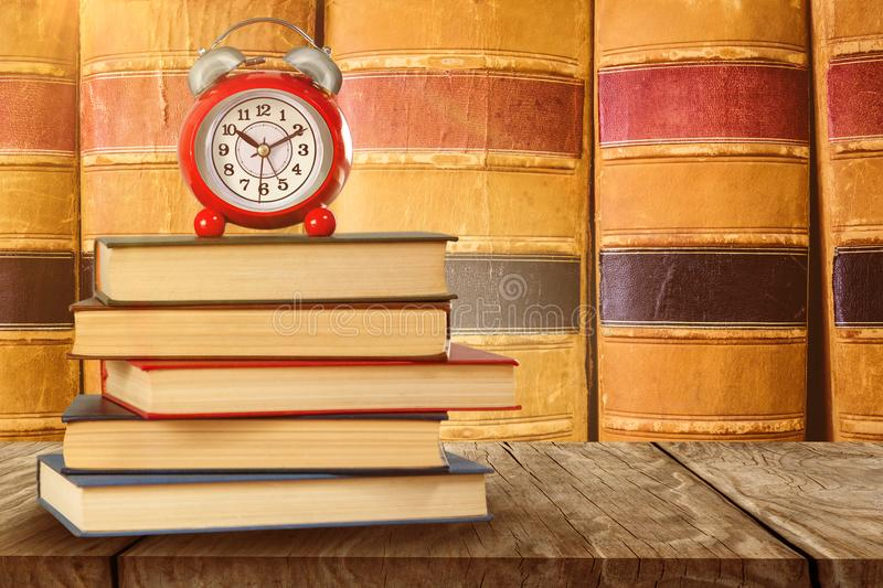 Composite image of old alarm clock and stack of books. Old alarm clock and stack of books against close up of old books stock photo