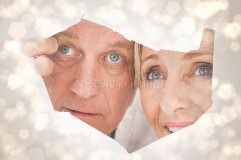 Composite image of older couple looking through rip. Older couple looking through rip against light glowing dots design pattern royalty free stock photography