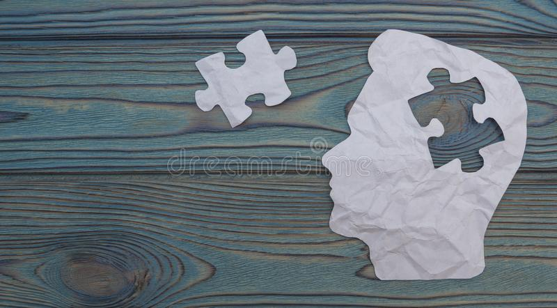Composite image of paper in the form of a head on a wooden background. royalty free stock image
