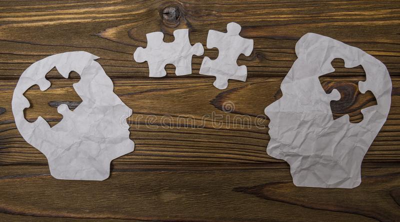 Composite image of paper in the form of two head silhouettes on a wooden background. royalty free stock photos