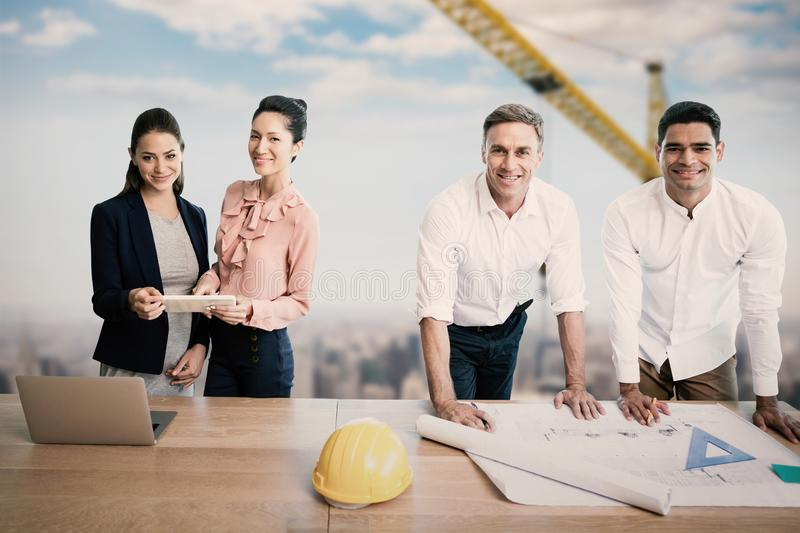 Composite image of portrait of architects at table stock image