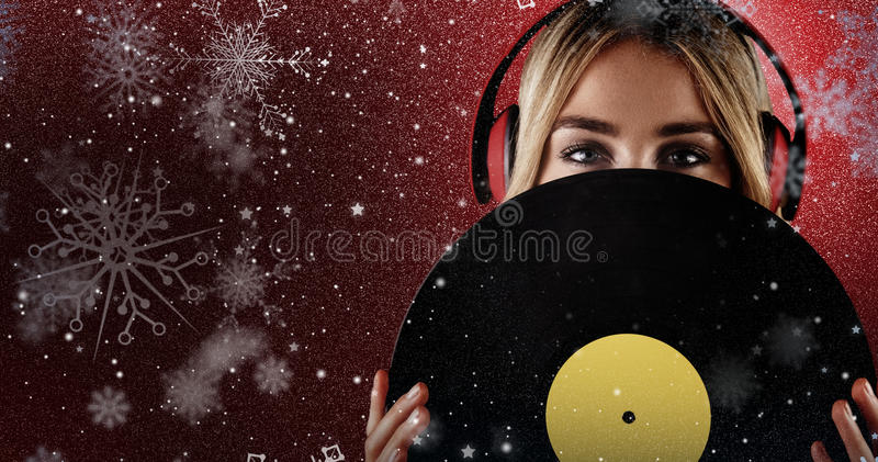 Composite image of portrait of a beautiful woman holding a vinyl royalty free stock photo