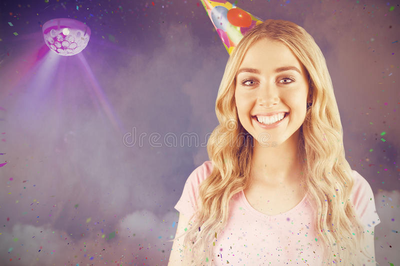Composite image of portrait of a beautiful woman with party hat stock photography