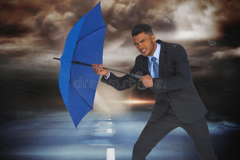 Composite image of portrait of businessman defending with blue umbrella stock photography