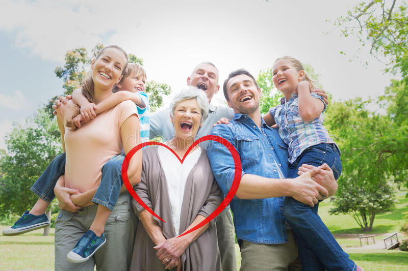 Composite image of portrait of cheerful extended family at park royalty free stock photography