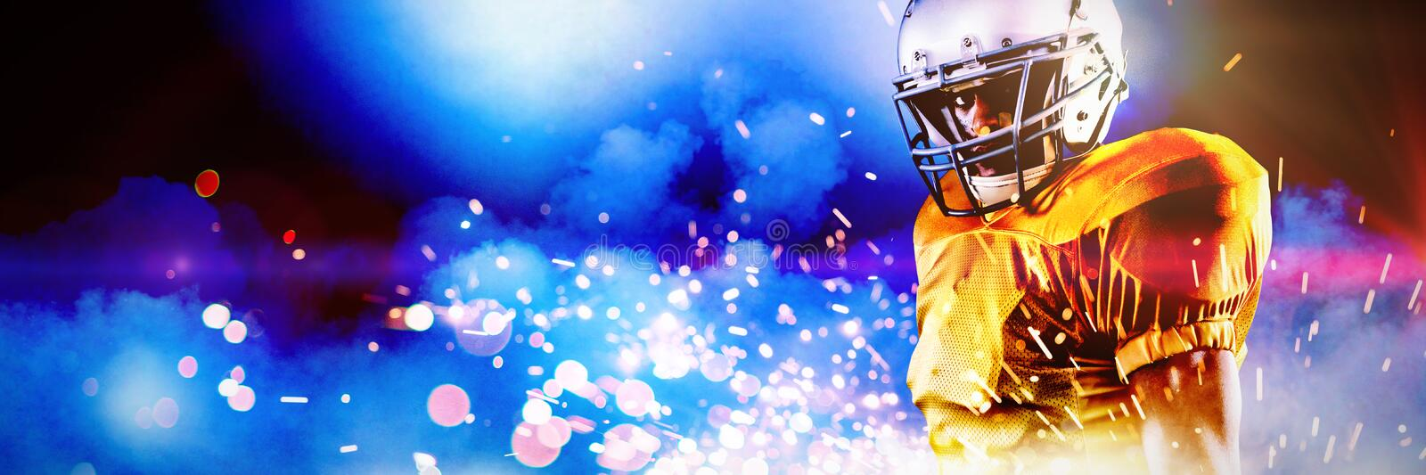 Composite image of portrait of confident american football player in helmet holding ball royalty free stock photography