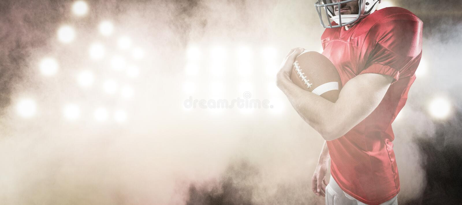 Composite image of portrait of confident american football player in red jersey holding ball royalty free stock photos